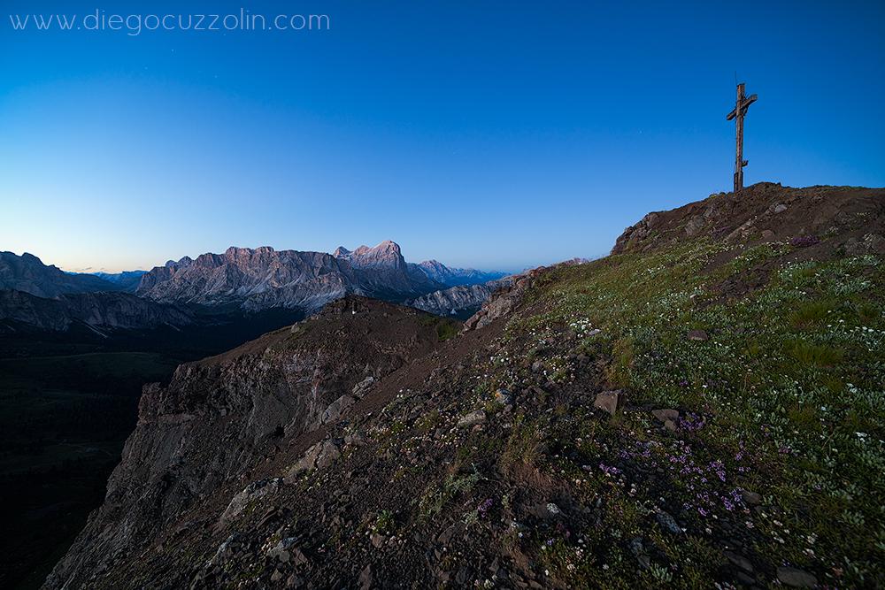 la croce di vetta del Col di Lana, con in fondo le Tofane, all'ora blu