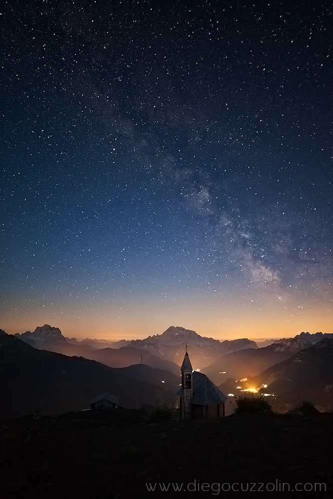 cielo stellato e Via Lattea verso Pelmo e Civetta, in basso le luci della Valle del Cordevole