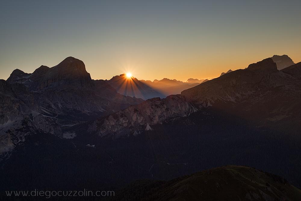i primi raggi del sole spuntano dietro il Cristallo
