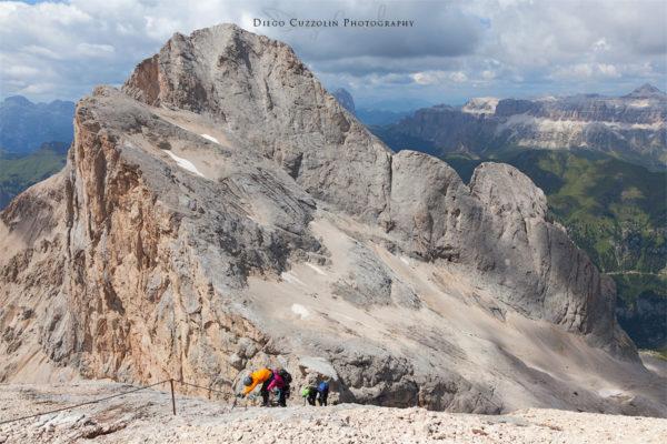 Escursionisti che scendono lungo la ferrata, col Gran Vernel sullo sfondo