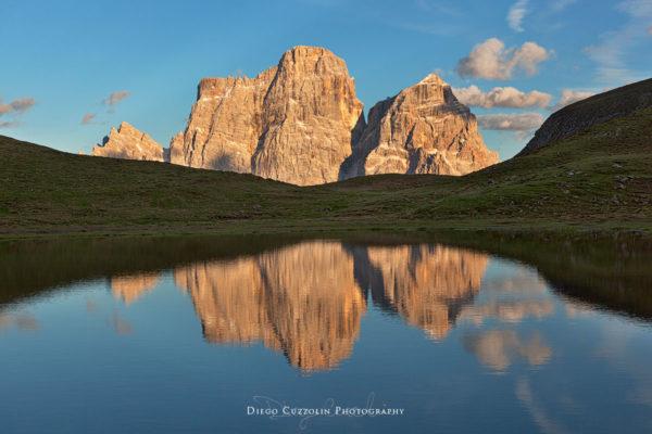 Il riflesso sulle acque del Lago delle Baste raddoppia la belleza del Pelmo infuocato dall'enrosadira